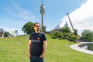 Bernhard Goodwin im Olympiapark (mit Olympiastadion und Olypiaturm im Hintergrund)