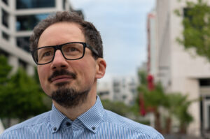 Bernhard Goodwin blickt vor modernen Wohnhäusern in die Ferne