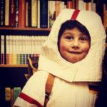 Bernhard Goodwin als Kind in Astronautenverkleidung vor einer Bücherwand.